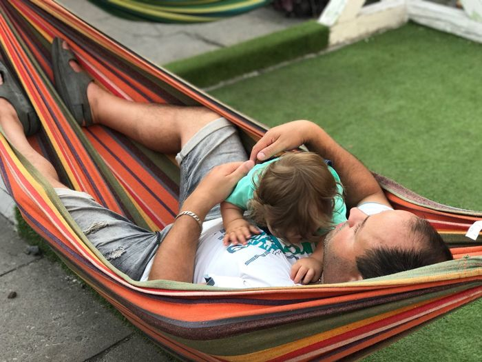 High angle view of father embracing baby while lying in hammock