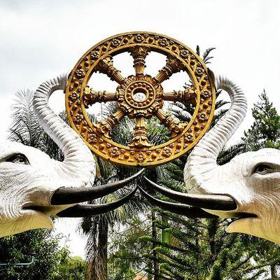 Sepasang patung gajah putih yang mengusung roda Dharma / Statues of white elephants carrying the wheel of Dharma.