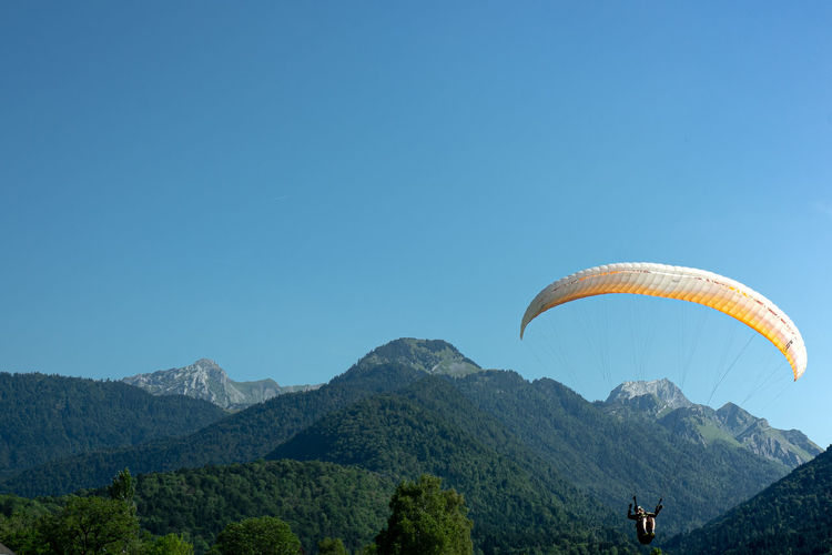 Man paragliding over mountains against clear sky