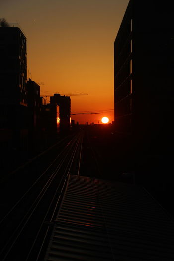 Railroad tracks amidst buildings against sky at sunset