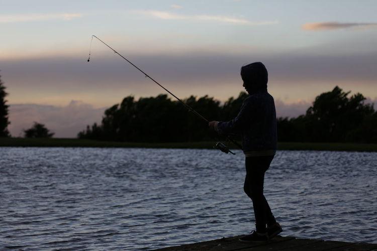 Boy fishing on lake against sky during sunset