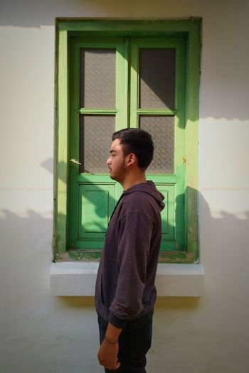 Side view of young man looking away while standing against window