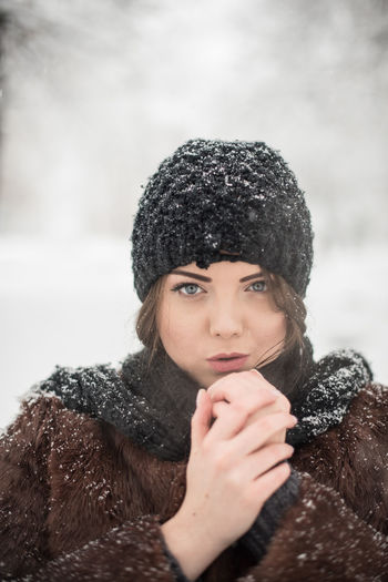 Close-Up Portrait Of Young Woman Standing In Snow
