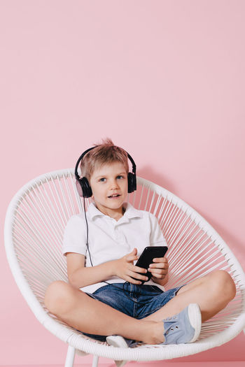 Little boy in headphones using smartphone Casual Chair Fun Headphones Music Pink Reading Sitting Adorable Background Boy Child Concentrationcamp Kid Legs Crossed Looking Mobile Playing Smartphone Technology Using White Wireless Woven