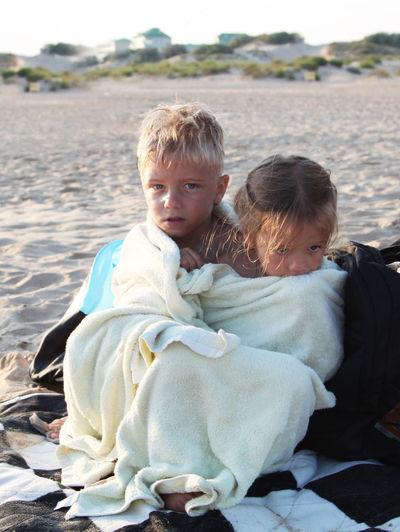 Brother and sister covered with towel at beach. Photos happy kids in the summer on the sand Blond Hair Bonding Boy Child Childhood Day Family Family Bonds Happiness Holiday Kid Outdoors People Portrait Sand Sister Smiling Togetherness Towel Two People Water