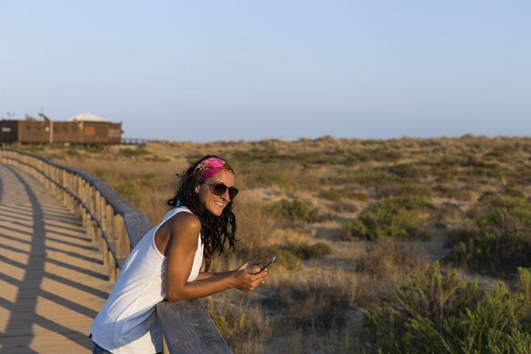 Portrait of smiling woman holding phone on footbridge