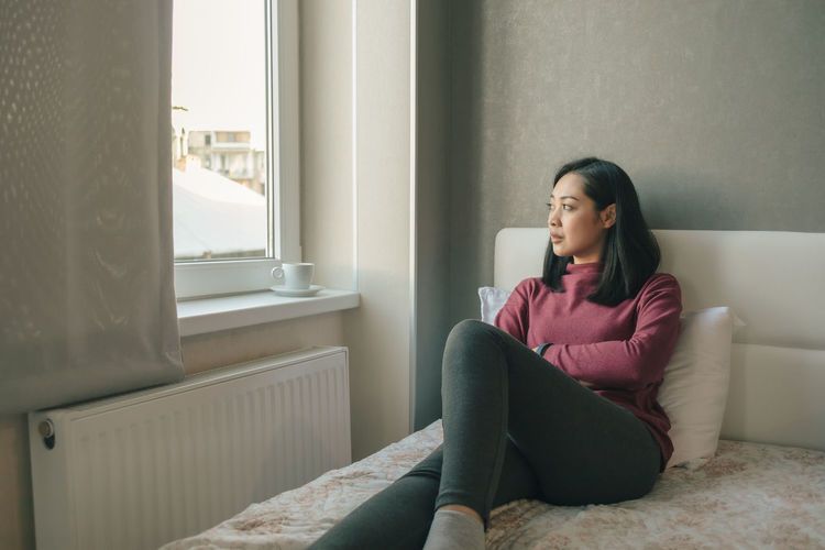 Woman looking away while sitting on sofa at home