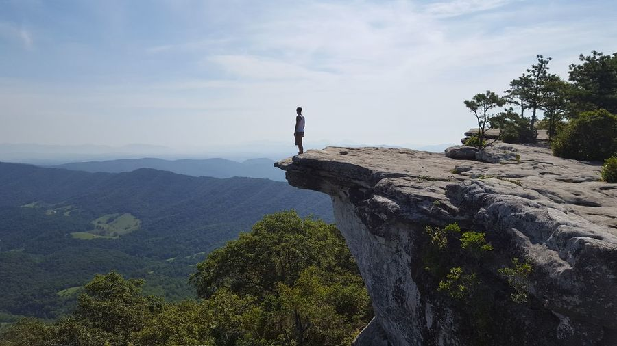 Man standing on cliff against sky