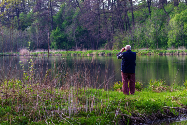 Lonely old man observes birds. Old Man Beauty In Nature Birds Casual Clothing Fishing Fishing Rod Full Length Grass Holding Lake Leisure Activity Men Nature Observes One Person Outdoors Plant Real People Reflection Standing Tree Water