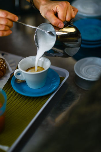 Cropped image of person pouring coffee in cup