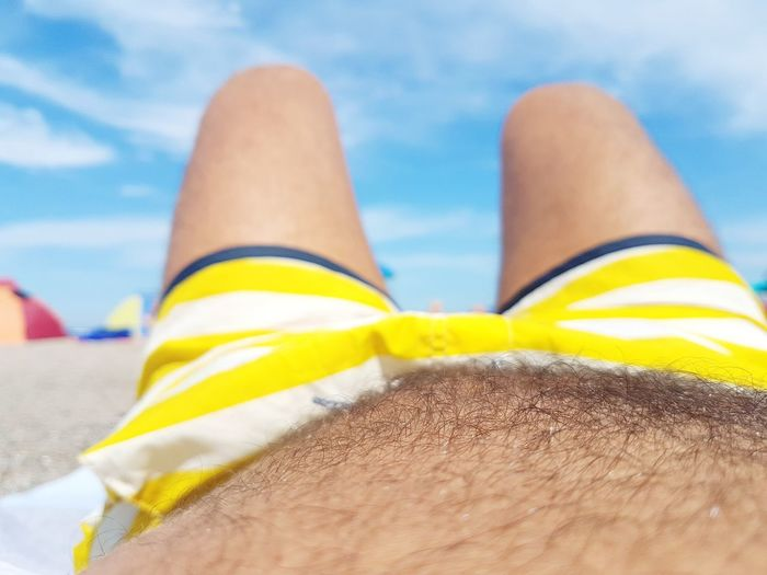 Midsection of man relaxing at beach against sky