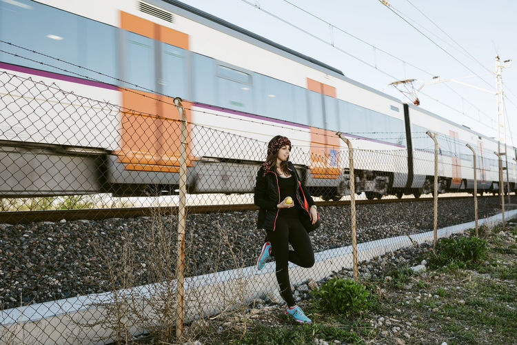 Woman Leaning On Chainlink Fence Against Train