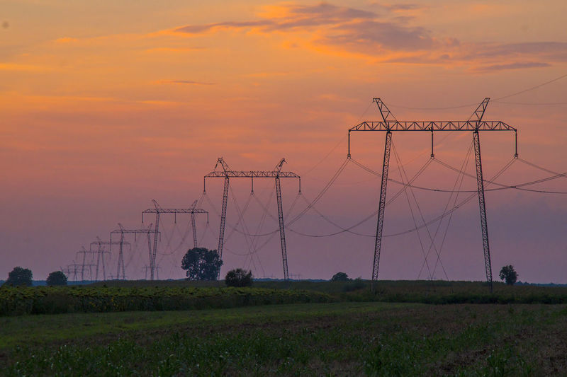 Power lines and pylons in red sunset Cable Cloud - Sky Electrical Equipment Electricity  Electricity Pylon Field Fuel And Power Generation Global Communications Land Landscape Nature No People Orange Color Power Line  Power Supply Scenics - Nature Sky Sunset Technology