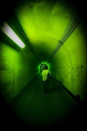 来る。 One Person Illuminated Indoors  Standing Lighting Equipment Full Length Real People Architecture Green Color Rear View Built Structure Tunnel Light - Natural Phenomenon Wall - Building Feature Light Light Fixture