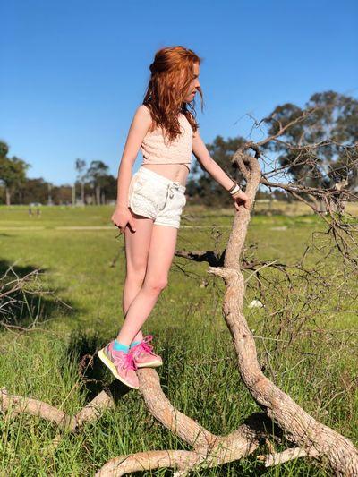 Girl standing on dead tree branch at grassy field