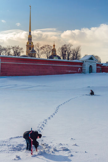 People ice fishing on snow covered field by peter and paul fortress