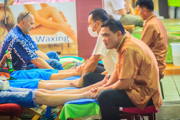 Bangkok, Thailand - March 2, 2017: Foot massage service in spa salon at Khao San Road night market, Bangkok, Thailand. Khao San Rd Khao San Road KhaoSan Khaosan Rd. Khaosandroad Tourist Tourist Attraction  Tourists Adult Casual Clothing Child Childhood Day Females Foot Massage Foot Massage Foot Massage Area Girls Group Of People Incidental People Khao San Khao San Knok Wua Khao San Rd. Khaosan Road Khaosanroad Leisure Activity Lifestyles Males  Men Night Market Night Market In Thailand Night Market, People Real People Side View Sitting Togetherness Tourist Destination Women