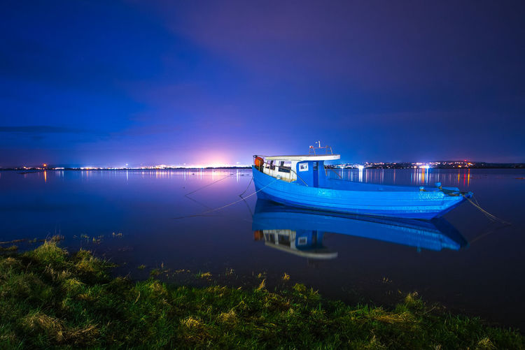 Boat moored on sea against sky at night