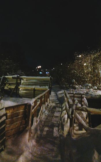 Crooked and Wobbly Wooden Gangway over the Trench in Snowy Winter Night in Murmansk Night Photography Night View