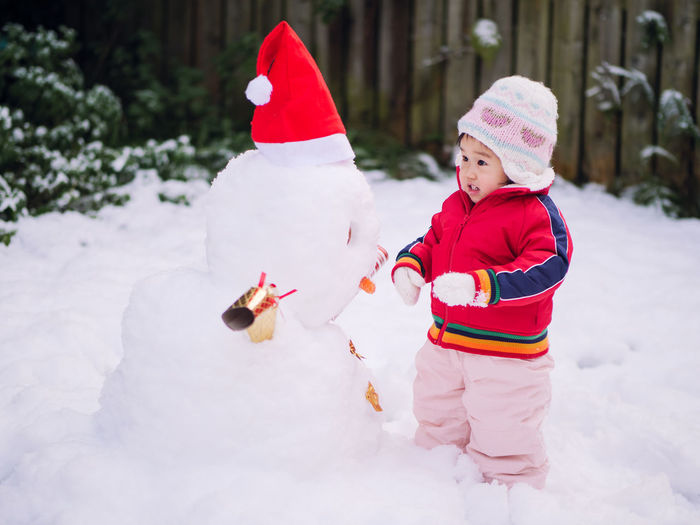 Cute Toddler Girl Standing By Snowman During Winter