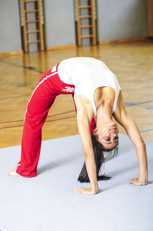 young beautiful woman Balance Day Exercising Flexibility Full Length Gym Handstand  Healthy Lifestyle Indoors  Leisure Activity Lifestyles One Person People Practicing Real People Self Improvement Skill  Sport Sports Clothing Strength Stretching Young Adult Young Women
