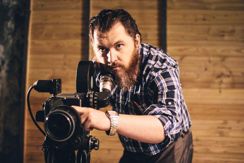 Mid adult man operating movie camera