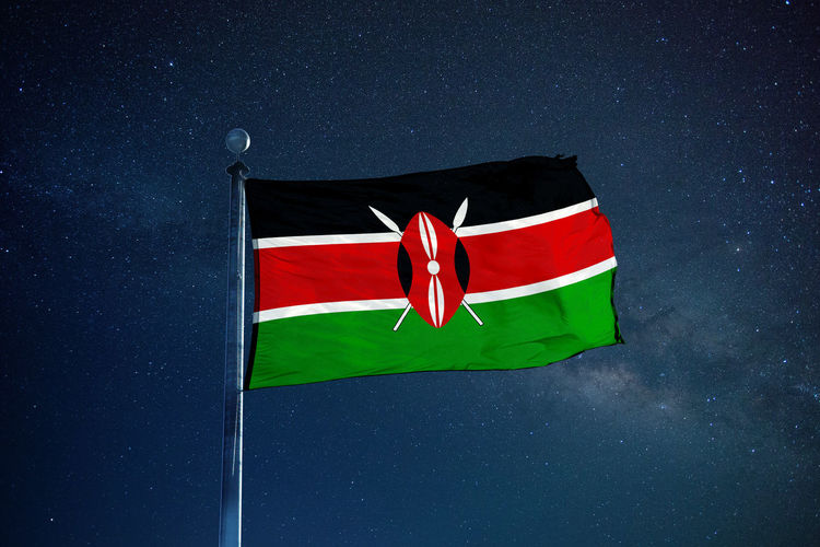 Low angle view of kenyan flag against star field sky