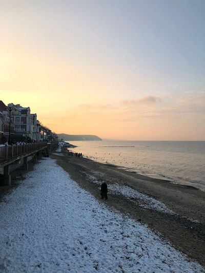 Snow covered beach against sky during sunset