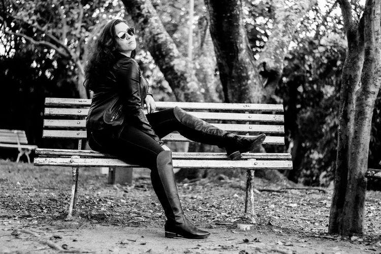 Full length of fashionable teenage girl sitting on park bench