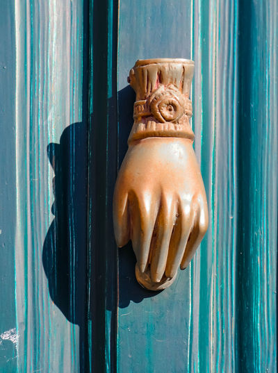 Antique ornate hand of fatima door knocker on distressed turquoise door in small town in Greece - originally used in Moslem households to protect house from evil eye Ancient Antique Evil Eye Mediterranean  Ancient Civilization Carved Charm Close-up Door Doorknocker Entrance Europe Greece Hand Hand Of Fatima Knock Knocker Moslem Muslim Old Ornate Superstition  Symbol Turquoise Colored Village