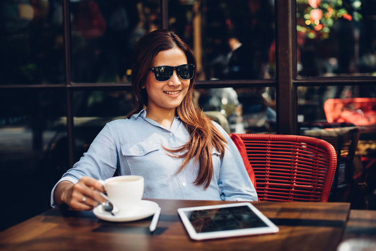Young woman wearing sunglasses while having coffee at restaurant