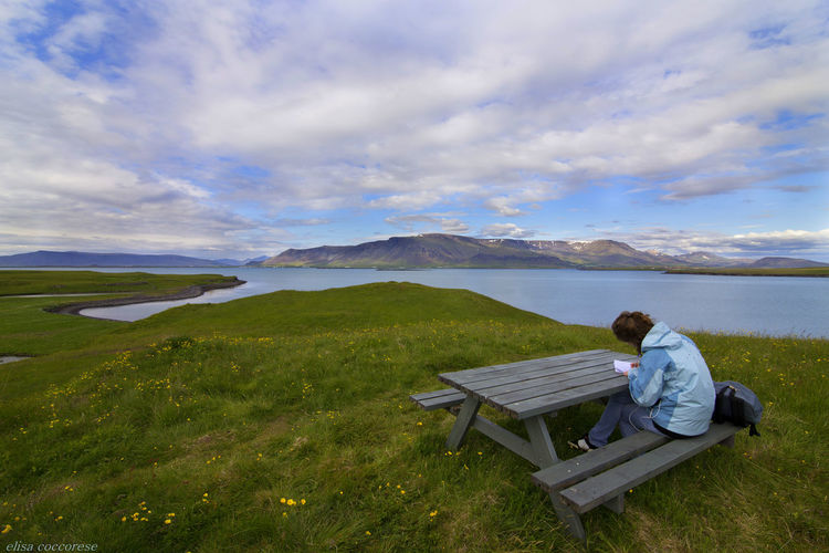 Woman reading book while sitting on picnic table by lake
