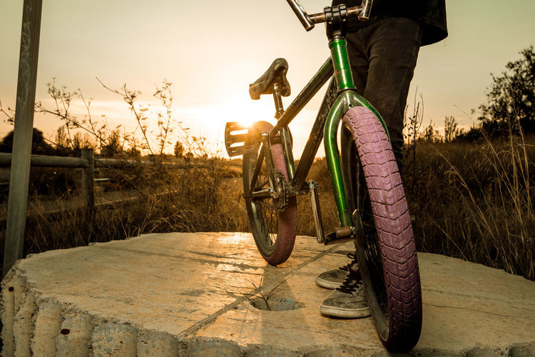 Low section of man cycling in bicycle at sunset