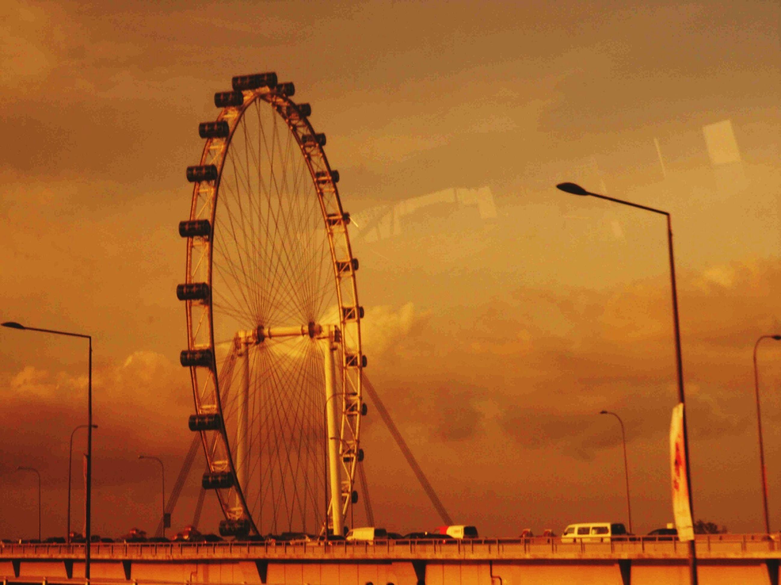 sunset, orange color, sky, low angle view, connection, cloud - sky, silhouette, built structure, architecture, outdoors, no people, dusk, nature, metal, cloud, cloudy, dramatic sky, electricity pylon, amusement park, ferris wheel