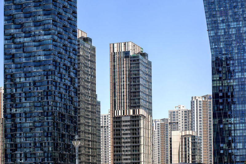 Low Angle View Of Tall Buildings Against Clear Blue Sky