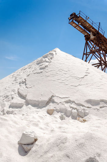 Heap of salt by machinery against blue sky