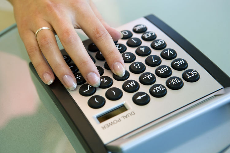 Close-up of human hand using calculator on table