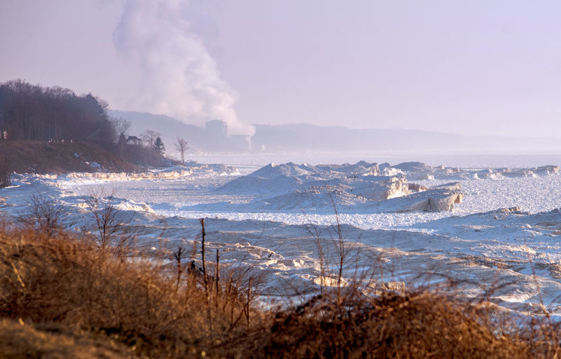 A frozen shore line on lake michigan, with the palisades nuclear plant in the background
