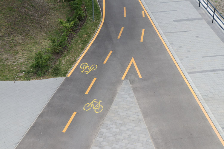 Bike path Arrow Symbol Communication Day Diminishing Perspective Direction Directional Sign Dividing Line Guidance High Angle View Marking Nature No People Number Outdoors Road Road Marking Sign Symbol Text The Way Forward Transportation