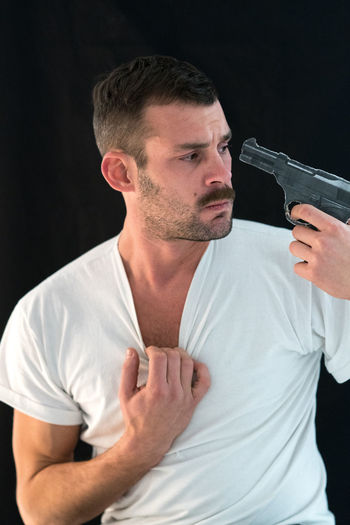 Man attempting suicide with gun against black background