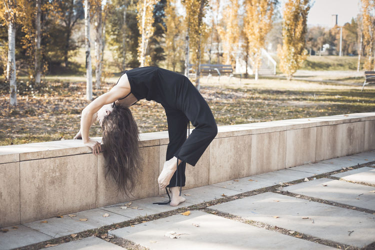 Side view of woman stretching at park during autumn