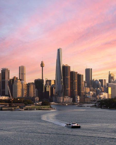 Wide cityscape of sydney at sunset showing the grown tower, international towers and others.