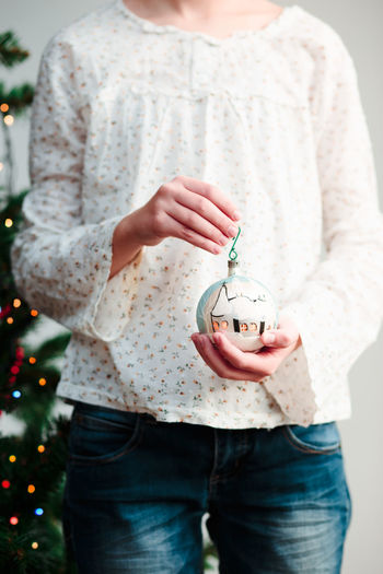 Midsection of woman holding christmas ornament while standing at home