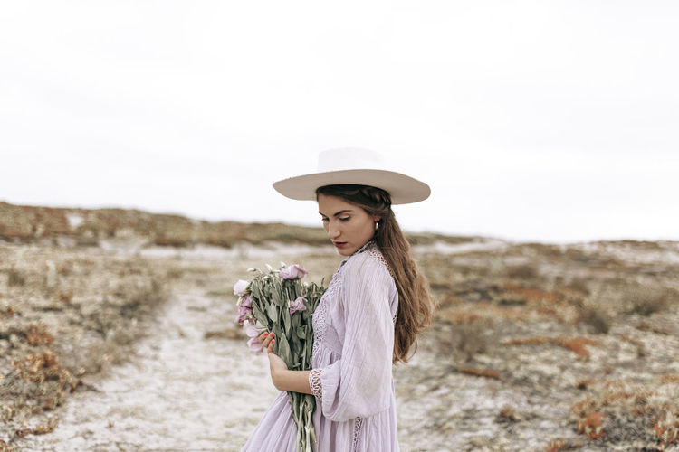 Woman wearing hat standing on land against sky