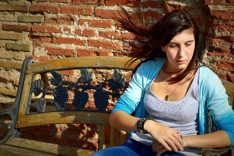 Young woman in front of brick wall
