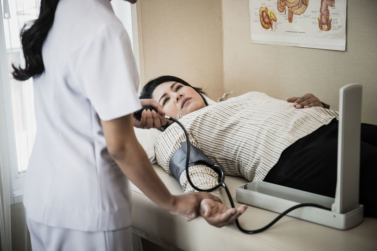Midsection of nurse examining blood pressure of woman lying on bed at hospital
