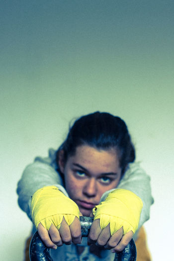 Close-Up Portrait Of Young Woman Holding Kettlebell