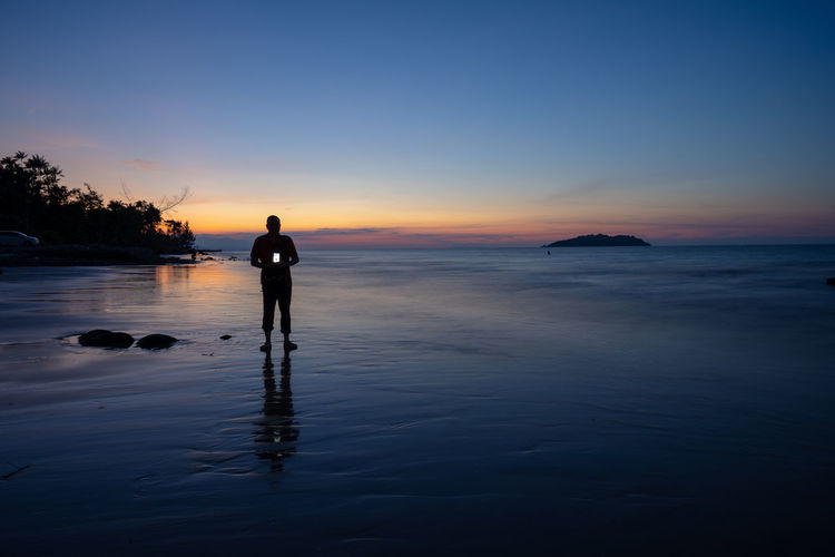 Silhouette man holding camera while standing at beach against sky during sunset