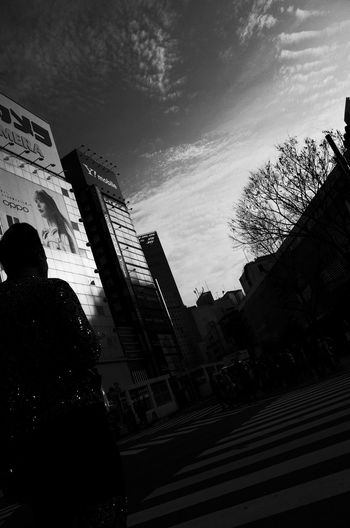 Low angle view of silhouette woman against buildings in city