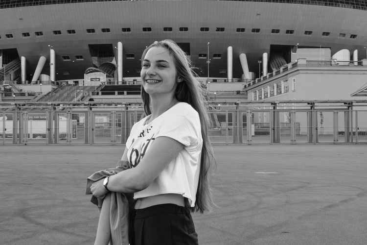 Portrait of smiling young woman standing in city